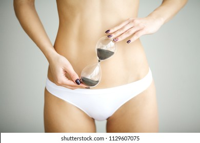 Woman holding sand clock over her stomach. Health hygiene sexual education concept.