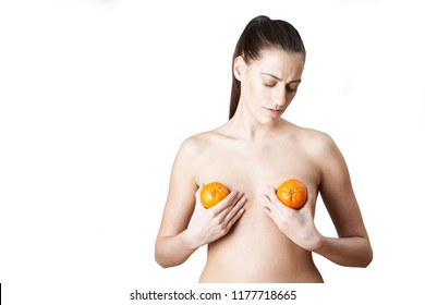 Woman Holding Satsumas To Illustrate Breast Enlargement Surgery