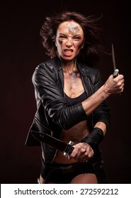 Woman holding a sharp knife with blood drops on face. Riot girl in leather jacket.