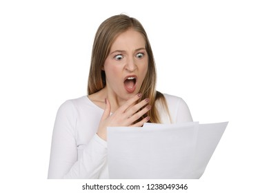 Woman holding a sheet of paper in her hands and looks horrified