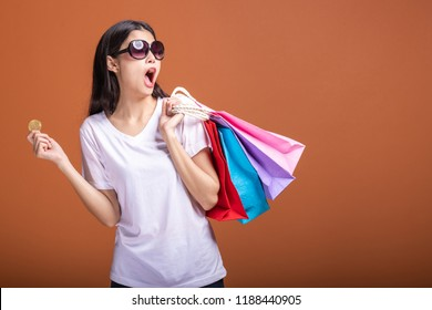 Woman holding shopping bag and bitcoin isolated in orange background. Young asian woman in white t-shirt, sun glasses in shock mood. Online currency shopping concept.