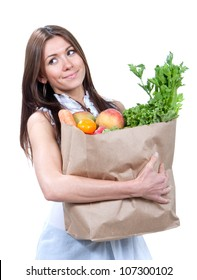 Woman holding a shopping bag full of fresh vegetables, mango, salad, asparagus, radish, avocado, carrots on white background
