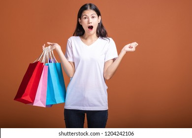 Woman holding shopping bag isolated in orange background. Young asian woman in white t-shirt, shock mood. Shopping concept.