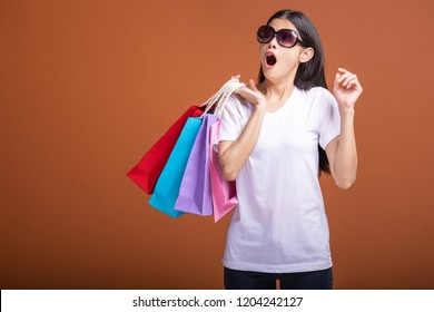 Woman holding shopping bag isolated in orange background. Young asian woman in white t-shirt, very shock mood. Shopping concept.