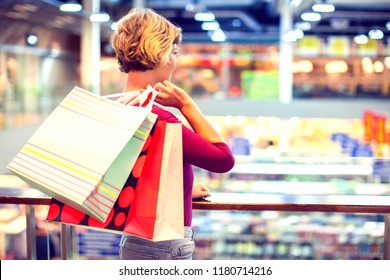 Woman holding shopping bag in the mall. Close up shot. Shopping, sale concept