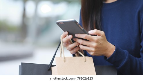 Woman holding shopping bag with mobile phone