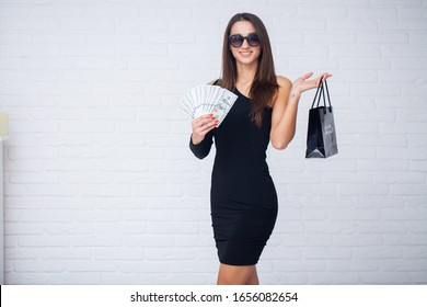Woman holding shopping bag on light background in black friday holiday