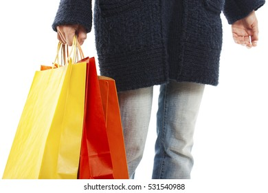 Woman holding shopping bags by hand. Isolated on white background