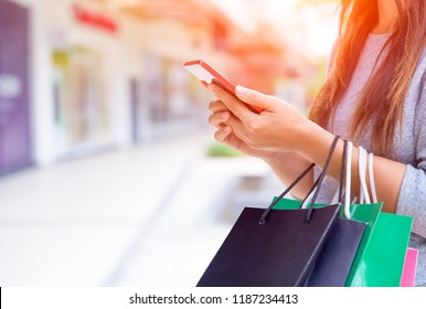Woman holding shopping bags doing online shopping on her mobile phone in the supermarket. Black Friday sale concept.