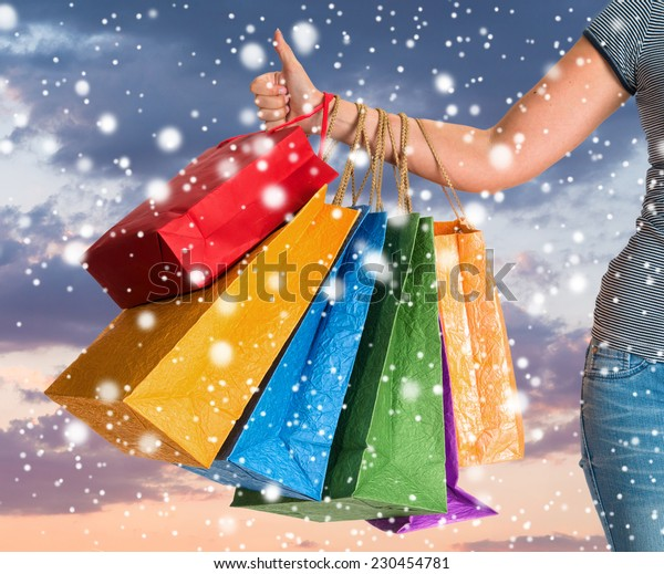 Woman holding shopping bags and gesturing thumb up. Christmas and holidays concept