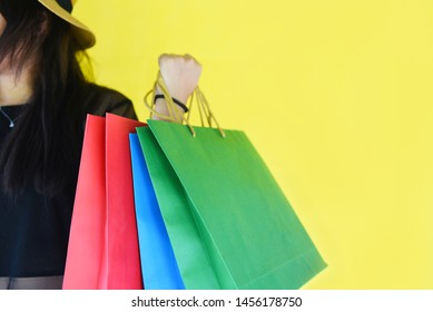 Woman holding shopping bags for girl fashion shopping in the summer colorful yellow background