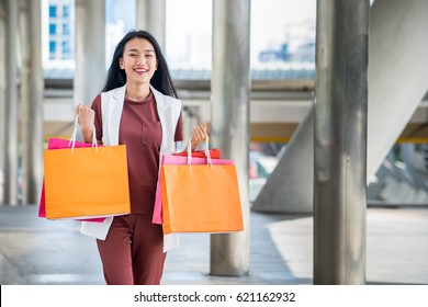 Woman holding shopping bags from the mall in the city. They feel happiness with her activity.