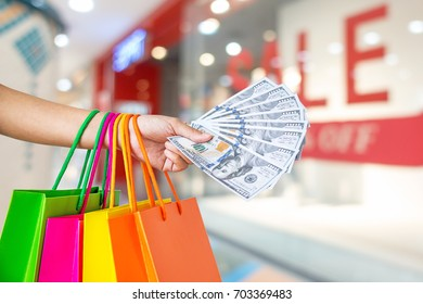 woman holding shopping bags in mall and money