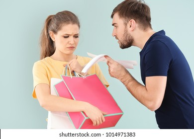 Woman holding shopping bags and man with bills arguing about money on color background. Problems in relationship