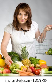 Woman holding a shopping basket in front of a display of fruits and vegetables, caucasian/white.