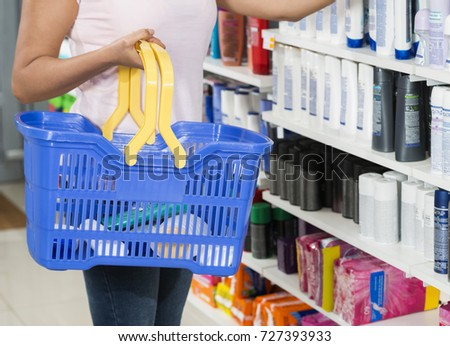 Woman Holding Shopping Basket In Pharmacy