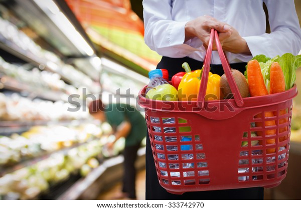woman holding shopping basket in supermarket