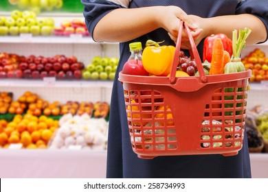 woman holding shopping basket in supermarket,fruit zone background