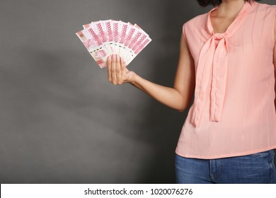 Woman holding and showing Indonesian money, rupiah in hand wearing peach clothes on grey background