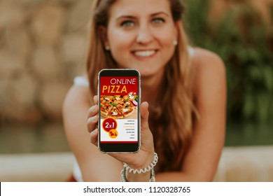Woman holding and showing a mobile phone with online pizza delivery service in the screen.