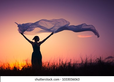 Woman holding silk cloth blowing in the wind. Freedom concept.