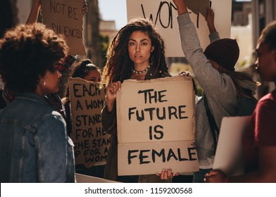 Woman holding a sing saying the future is female during a rally outdoors. Females protesting for their rights.