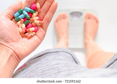Woman holding Slim pill in hand Standing weighing.Selective focus,Conception about health care