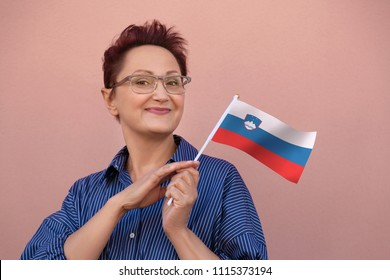 Woman holding Slovenia flag. Nice portrait of middle aged lady 40 50 years old with a national Slovenian flag over pink wall background.Learning Slovenian language. Visit Slovenia concept.