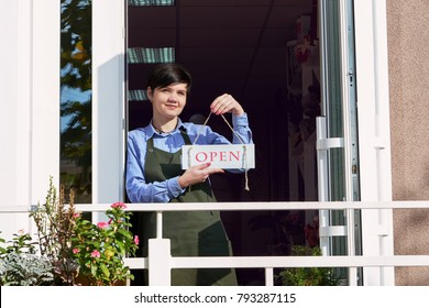 Woman holding small business. A smiling florist stands in the doorway of the store holding an open sign.