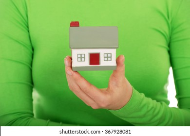 Woman holding small house.