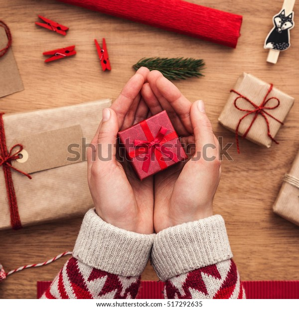 Woman holding small, red, christmas gift box over wooden desk with presents and decorations.