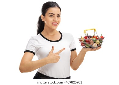 Woman holding a small shopping basket full of fruits and vegetables and pointing isolated on white background