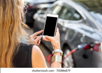 Woman holding a smart phone with empty screen to copy paste with electric car charging on the background