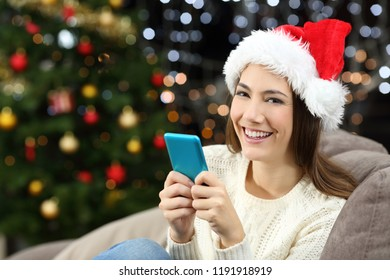 Woman holding smart phone looking at camera in christmas sitting on a couch in the living room at home