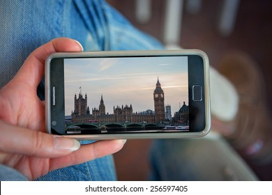 Woman, holding smart phone, looking at pictures from London on sunset, indoor shot