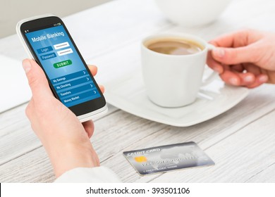 Woman holding smart phone with mobile banking application on a screen.
