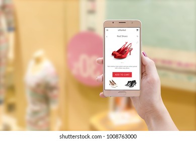 Woman holding smart phone with online store app on screen in front view. In background is window with discounts.