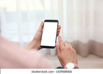 Woman holding smartphone with blank screen indoors, closeup of hands. Space for text