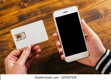 Woman holding smartphone and new SIM card, mock up image
