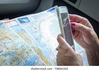 woman holding a smartphone and a paper map getting directions