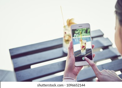woman holding smartphone and photograph juice on swimming pool in vacation and summer time.