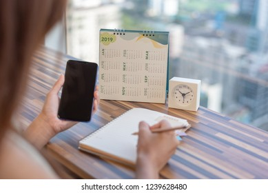 Woman holding smartphone to update calendar 2019 with notebook pencil diary on table with blurred background. Planning scheduling agenda event appointment for year 2019. Calendar and Planning concept.