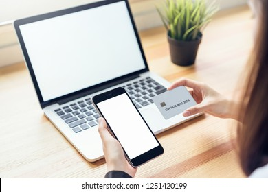 woman holding smartphone and using laptop on table in office room on windows with trees and nature background, for graphics display montage. Take your screen to put on advertising.