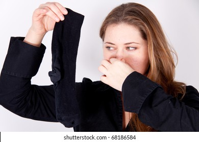 A woman is holding a smelly sock