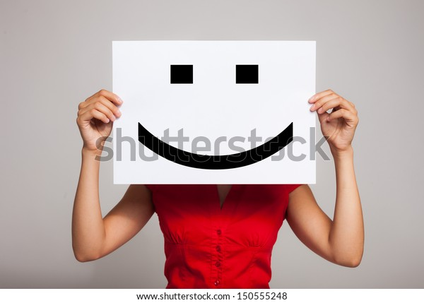 Femme tenant un émoticône de visage souriant