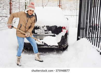 Woman holding snow shovel and cleaning  path  by snow