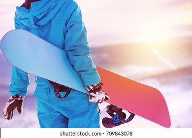 Woman holding snowboard in hands. Closeup view. Snowboarder or snowboarding concept at sunrise or sunset time