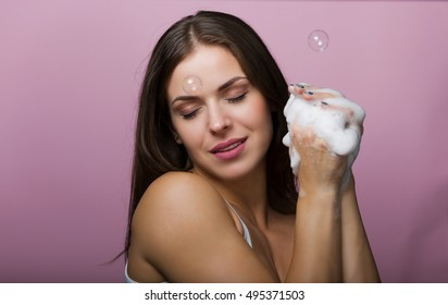 Woman holding a soapy sponge and washing her face