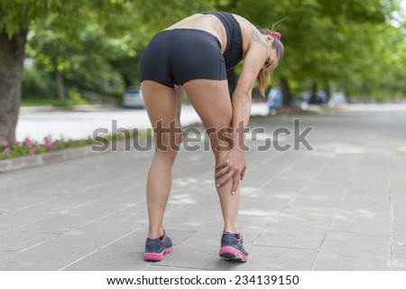 1e61f10be7 Woman holding sore leg muscle while jogging. Cramp in leg calves. Sports  injury concept