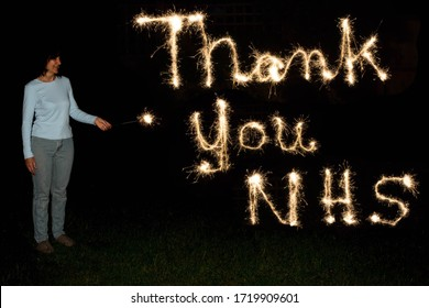 Woman holding a sparkler firework who has written the message of 'Thank You NHS' against a dark background, for their efforts during the Covid-19 pandemic.
